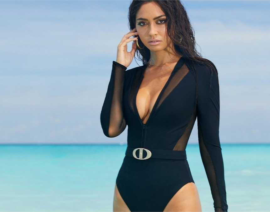 model on the beach wearing a black long sleeve scuba swimsuit with a belted waist.