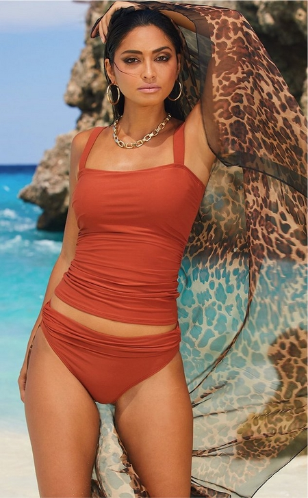 model on the beach wearing a rust colored tankini top with bikini bottoms and a gold chain necklace