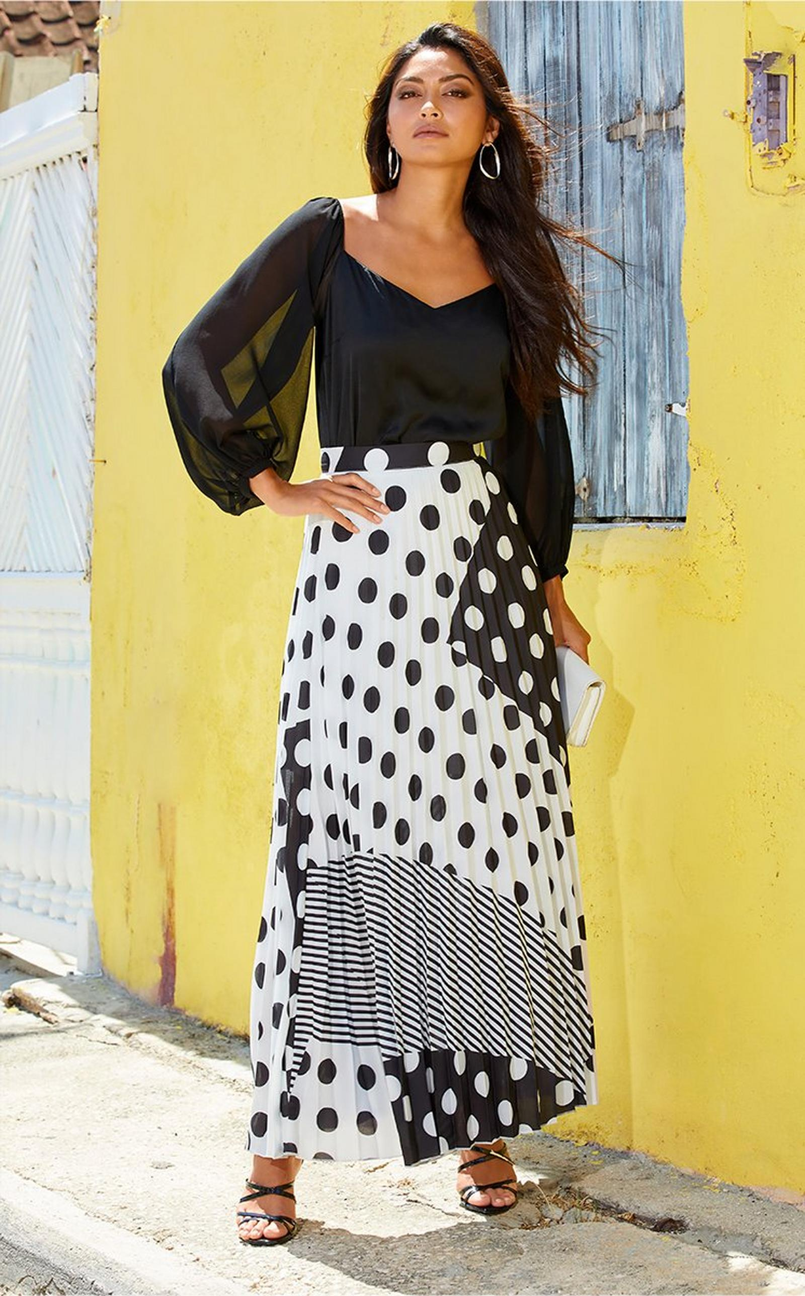 model wearing a black illusion sleeve top with a mixed print black and white maxi skirt and black strappy heels.
