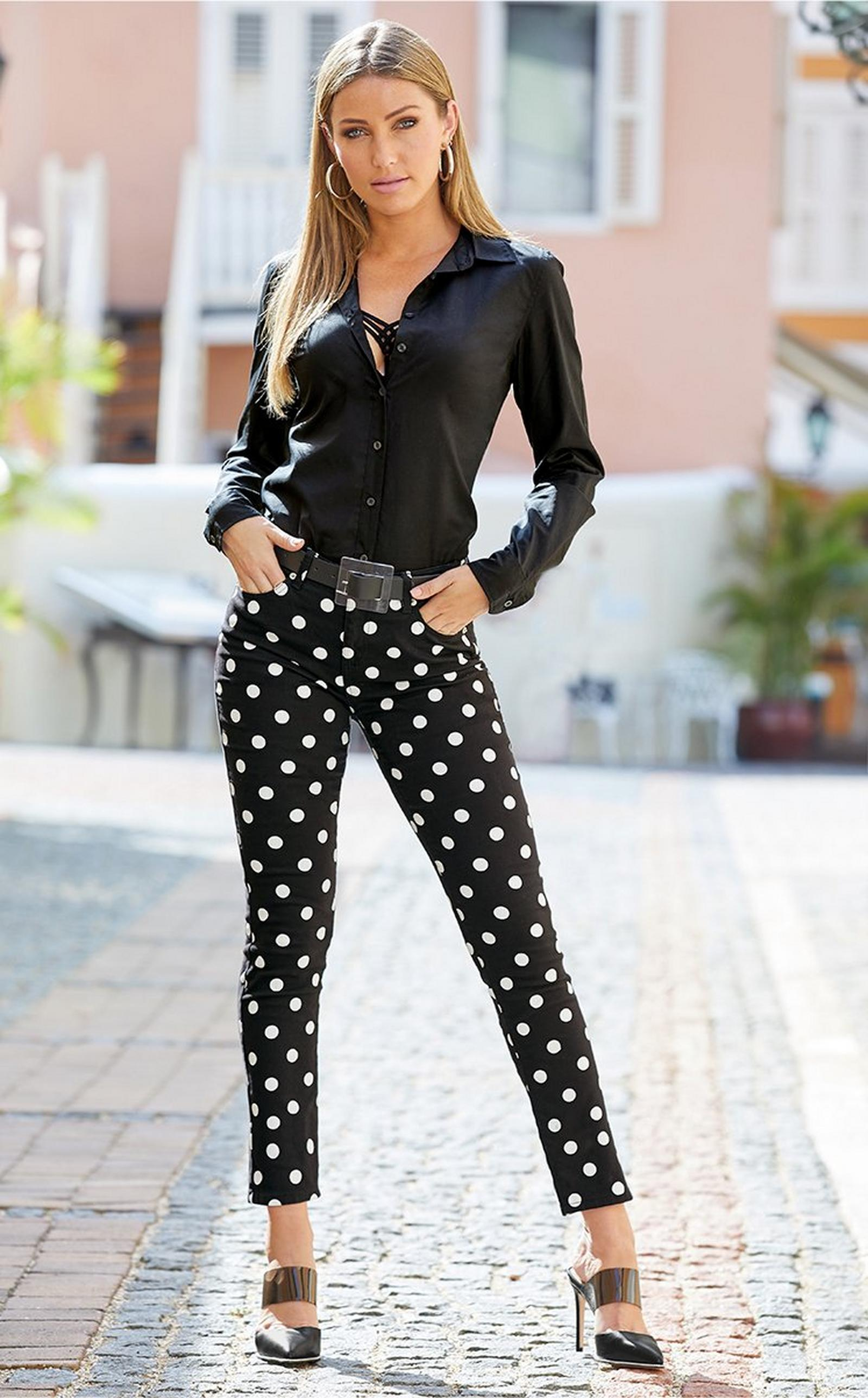 model wearing a black button-up top, strappy bra, clear belt, black and white polka dot jeans, and black vinyl heels.
