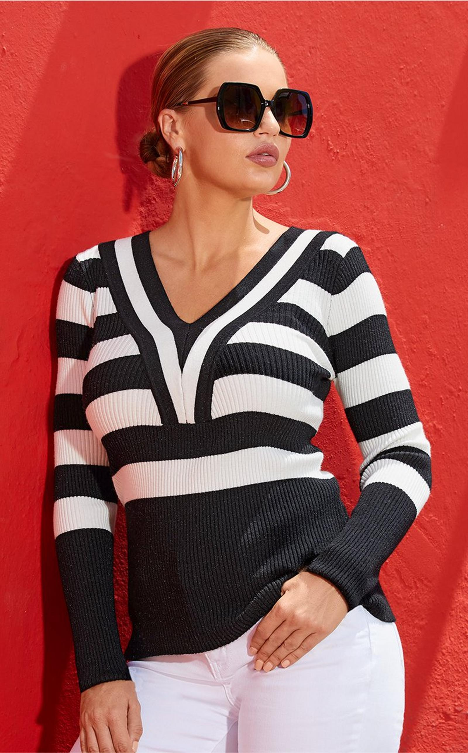 model leaning against a red wall wearing a black and white striped sweater, white jeans, and statement sunglasses.
