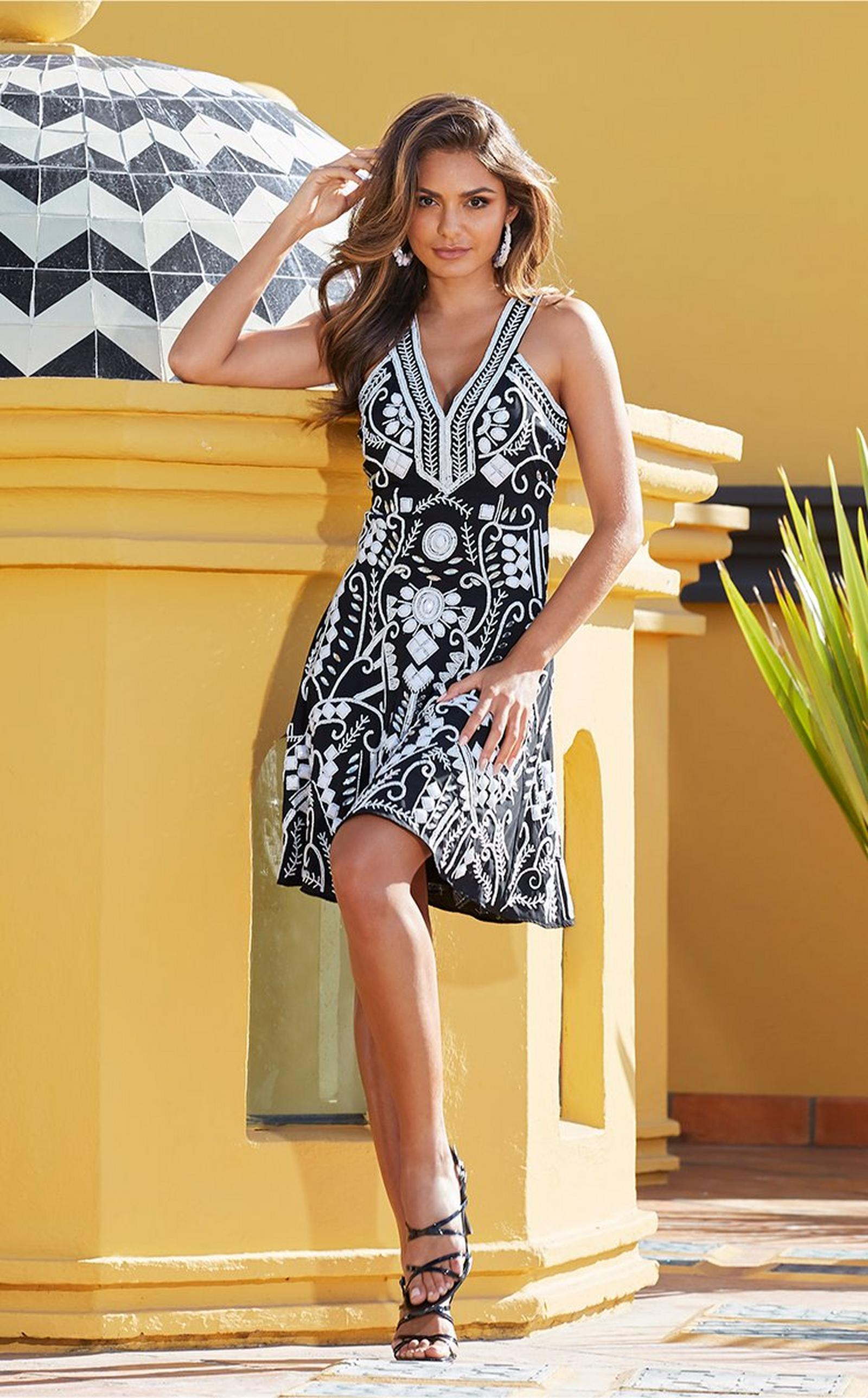 model wearing a black and white embellished dress and strappy black heels.