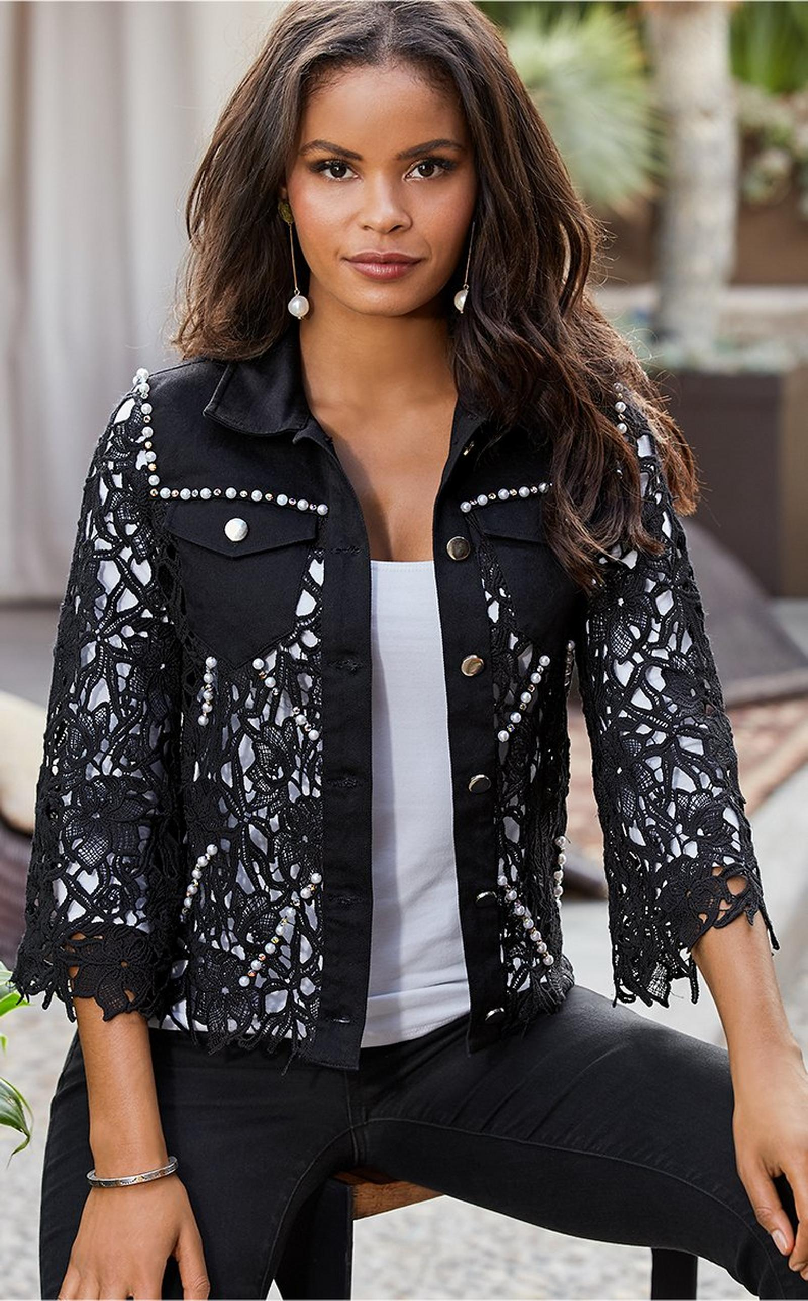 model wearing a black lacey embellished denim jacket over a white tank top and black jeans.