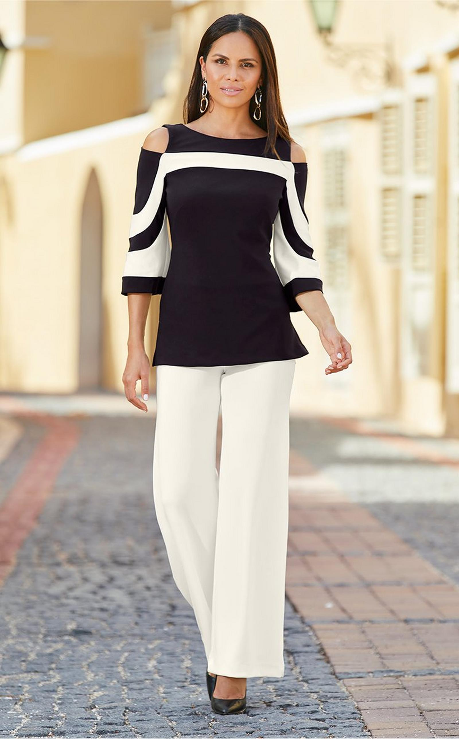 model wearing a black and white cold-shoulder top with off-white palazzo pants and black pumps.