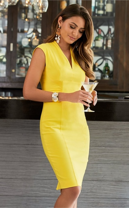 model wearing a sleeveless yellow dress and gold cuff while holding a martini.
