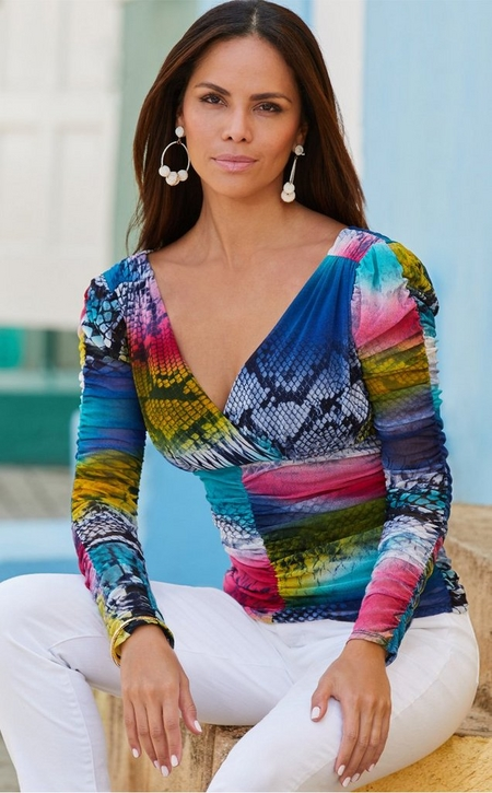 model wearing a multicolored animal print long-sleeve top and white jeans.