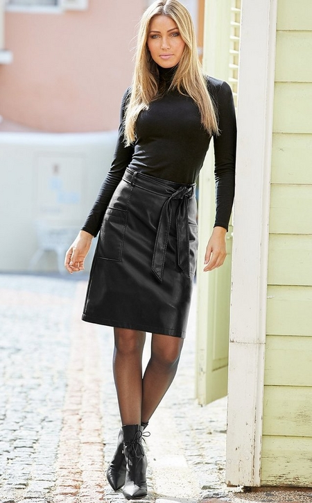 model leaning against a wall wearing a black long sleeve turtleneck, black leather skirt, sheer black tights, and black heeled booties.