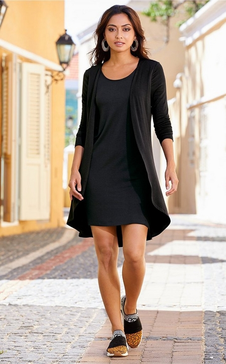 model wearing a black twofer duster and dress with animal print slip-on sneakers.