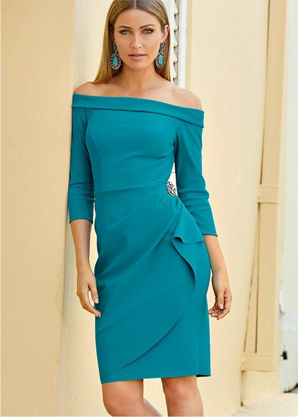 model wearing an off-the-shoulder teal compression dress with a jeweled brooch.