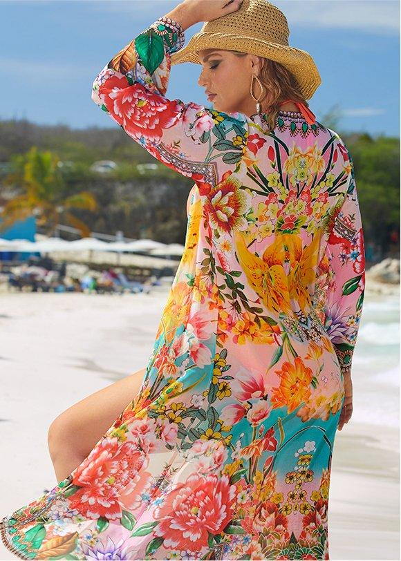 model wearing a floral duster and straw hat.