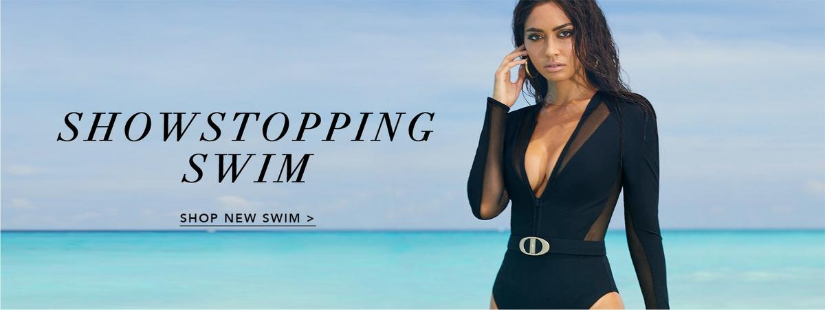model standing on the beach wearing a black scuba one-piece swimsuit that has belt around the waist and a deep v-neck.