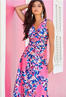 model wearing a ruched pink maxi dress with a blue floral pattern.