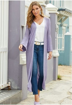 model wearing a lavender sweater duster over a white v-neck tank top, white belt, and a pair of ankle jeans.