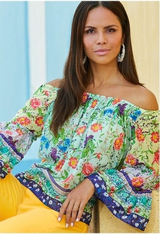 model wearing an off-the-shoulder floral top with yellow jeans.