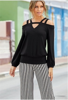 model wearing a black cutout cold-shoulder top and black and white striped palazzo pants.