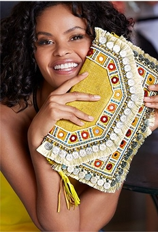 model holding a yellow embroidered clutch.