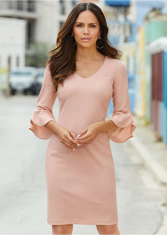 model wearing a blush flare-sleeve sheath dress.