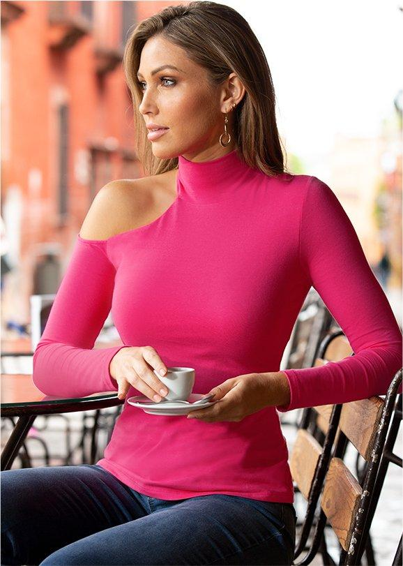 model wearing a mock-neck one-shoulder long sleeve top in hot pink and jeans.