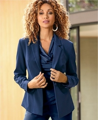 model wearing a navy cowl neck blouse, navy blazer, and jeans.