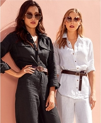 left model wearing a black linen jumpsuit, brown belt, and sunglasses. right model wearing a white linen button up top, brown belt, white linen pants, and sunglasses.