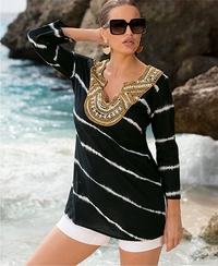 model wearing a black, white, and gold embellished tunic with white shorts and large sunglasses.