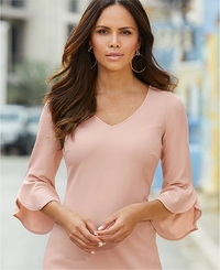 model wearing a blush flare-sleeve sheath dress.