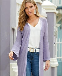 model wearing a lavender sweater duster, white tank top, white belt, jeans, and pastel earrings.