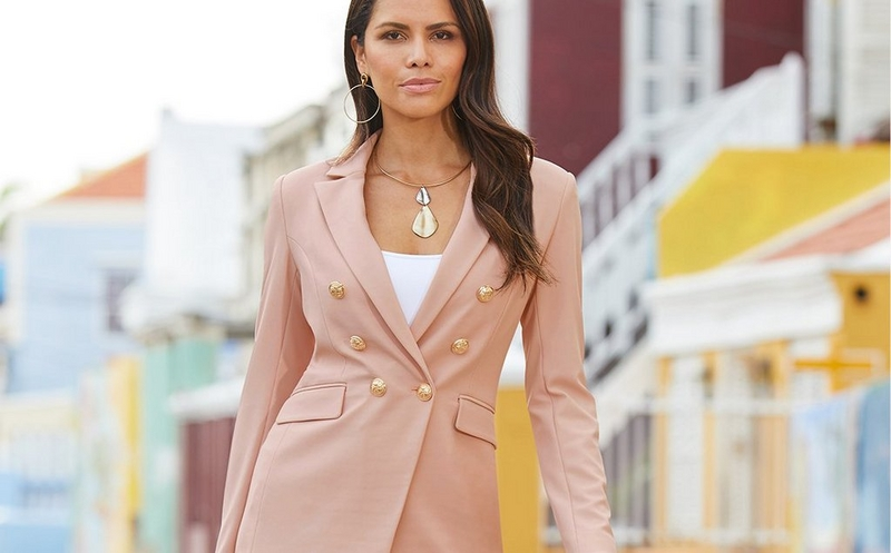 model wearing a blush blazer with gold buttons, a white tank top, and a metal choker necklace.