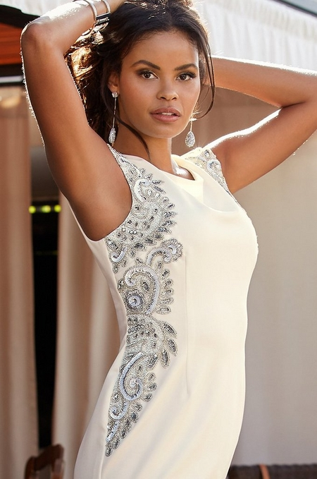 model wearing a sleeveless white dress with silver embellishments.