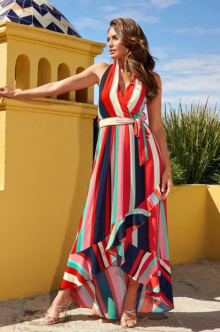 model wearing a multicolored, striped, halterneck maxi dress and silver strappy heels.