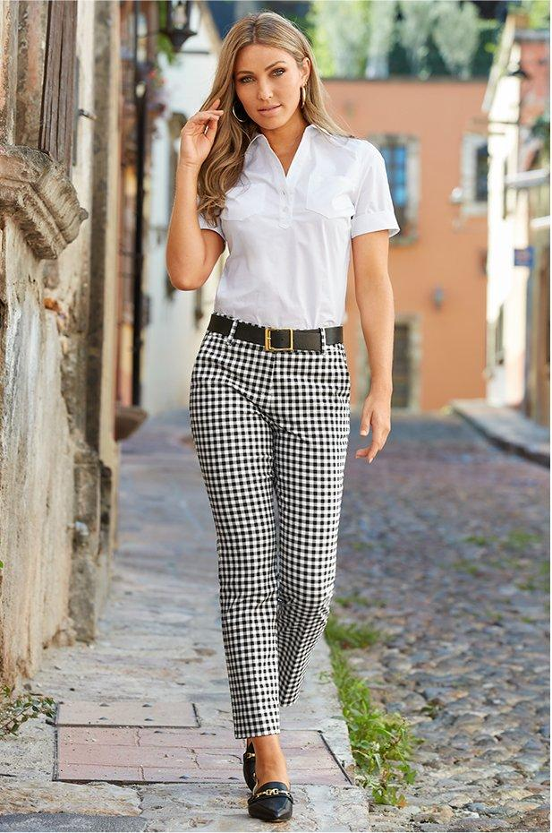 model wearing a white short sleeve button up shirt, black belt, black and white gingham crop pants, and sling-back loafer shoes.