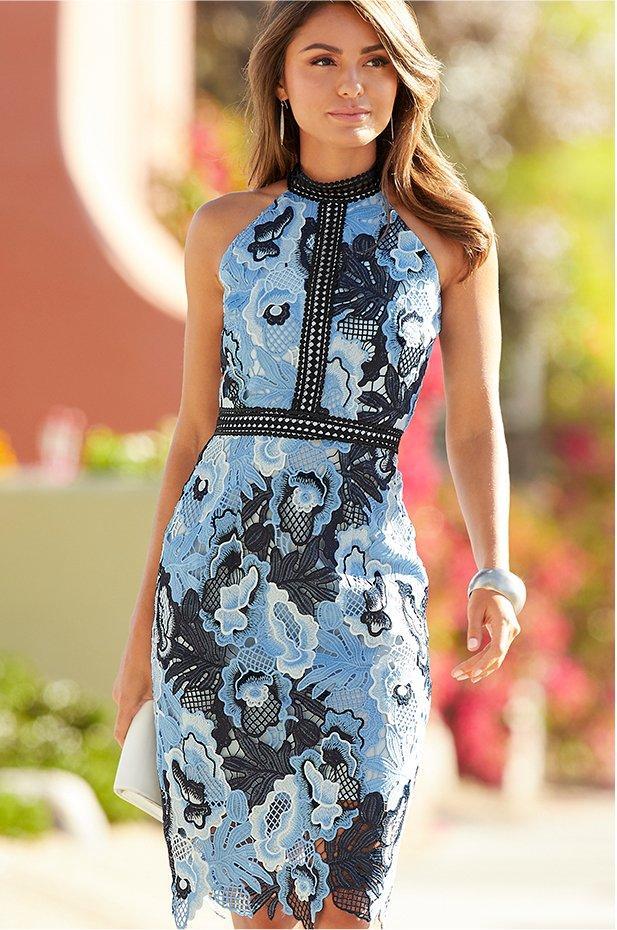 model wearing a mock neck lace midi dress in multiple shades of blue.