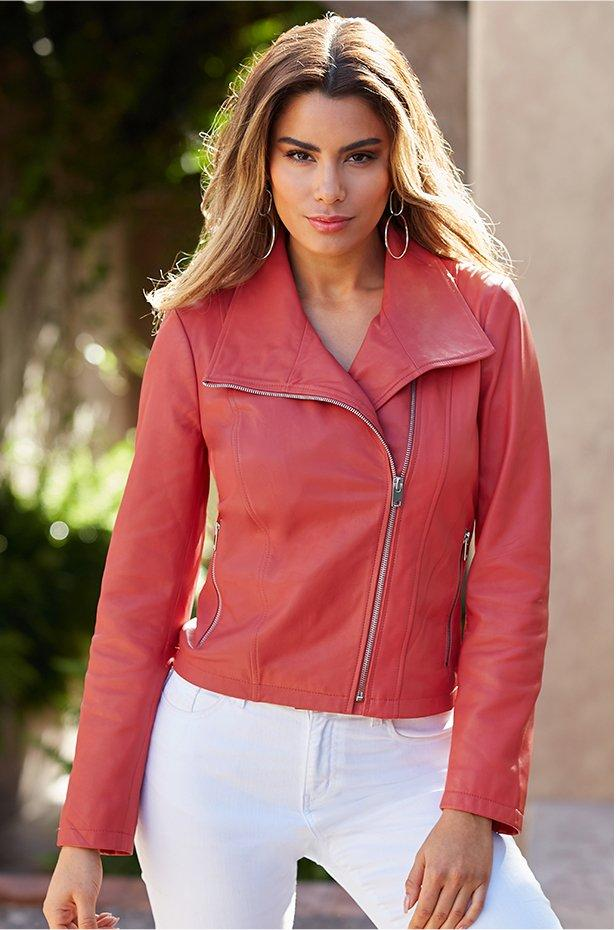 model wearing a coral collared moto leather jacket and white jeans.