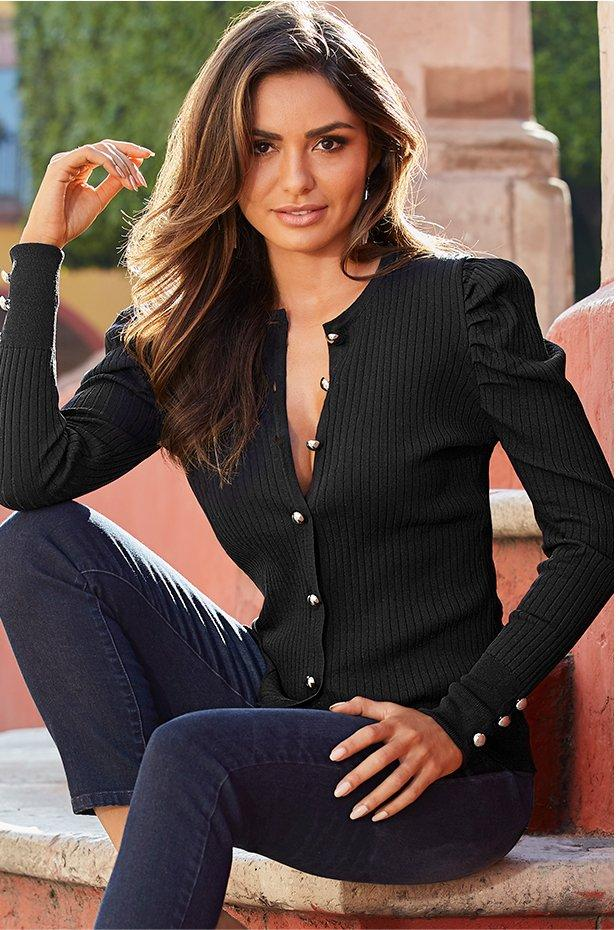 model wearing a black puff-sleeve cardigan with gold buttons and jeans.