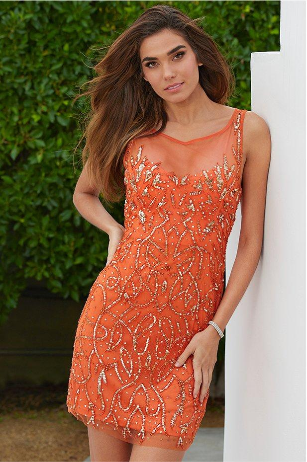 model wearing an orange illusion dress with gold sequin embellishments.