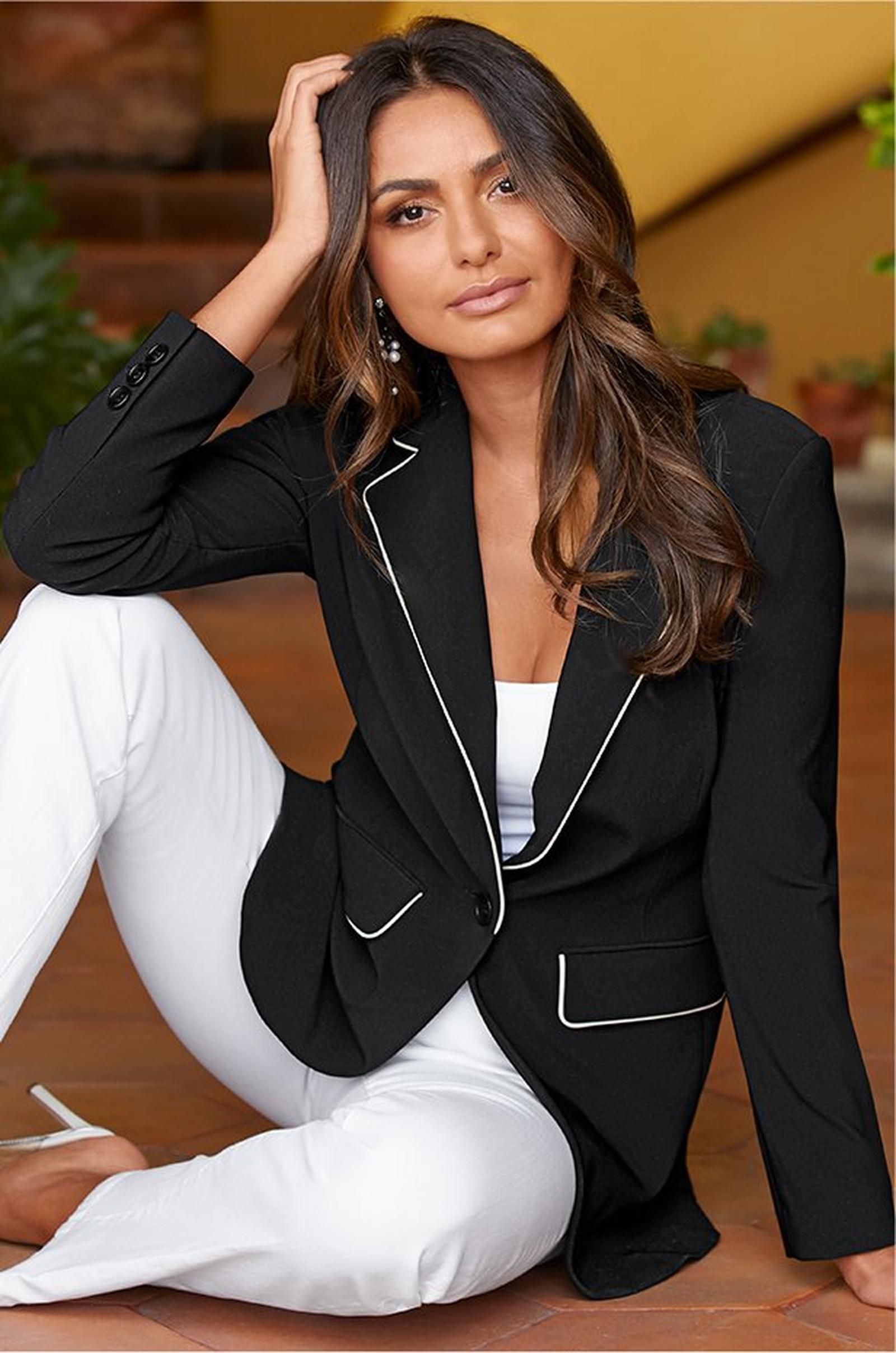 model wearing white pants, a white tank top, and a black blazer with white piping.
