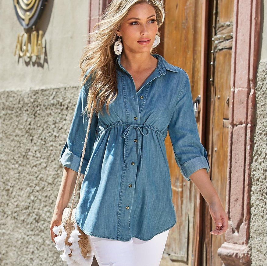 model wearing a tencel tie-waist top, white jeans, and a white tassel straw bag.