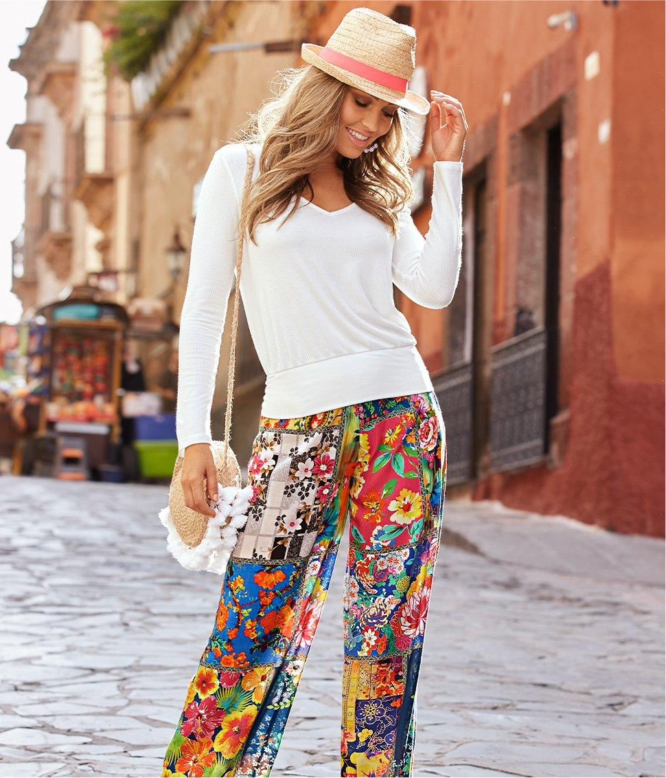 model wearing a straw hat, white sweater, and floral print palazzo pants white carrying a round bag with white tassels.