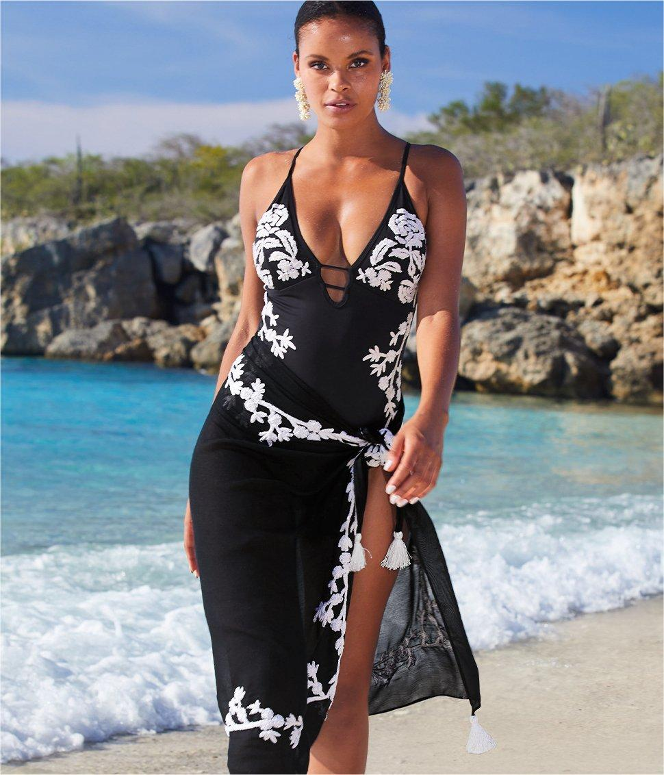 model wearing a black one piece swimsuit with white floral embroidery and a matching skirt cover up.