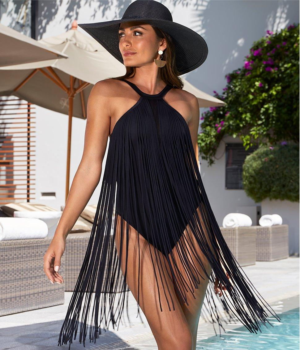 model wearing a black high-neck one-piece fringe swimsuit and a black floppy hat.