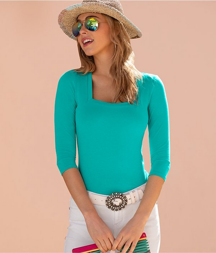 model wearing a three-quarter sleeve square neck top in teal, white jeans, white jeweled belt, and straw hat.