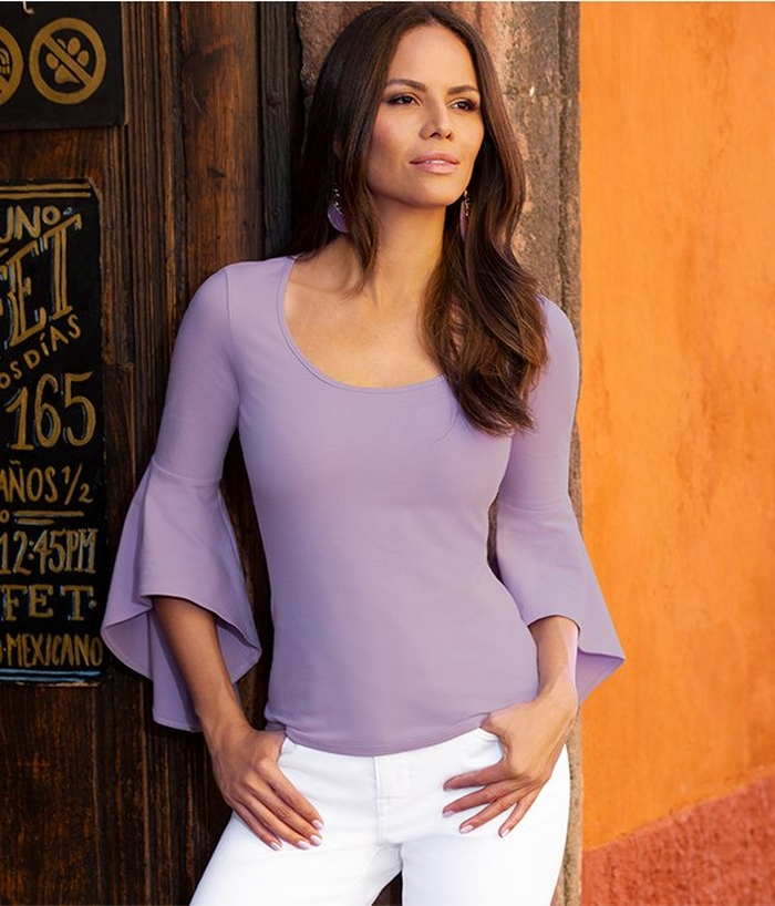 model wearing a lavender flare sleeve top and white jeans.