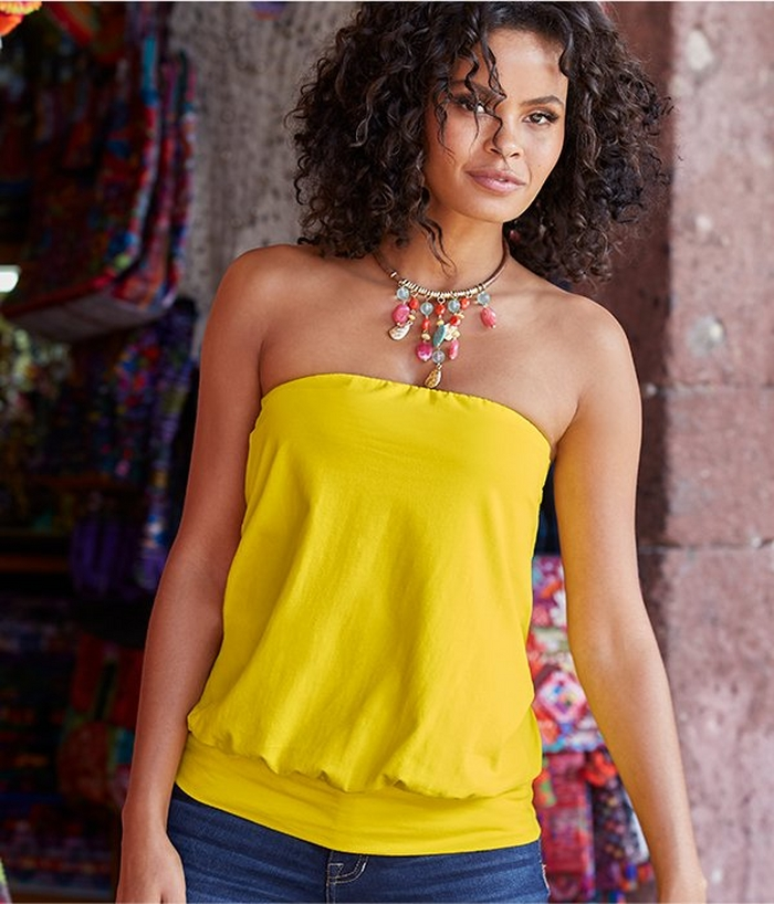 model wearing a yellow blouson tube top, multicolored jewel necklace, and jeans.