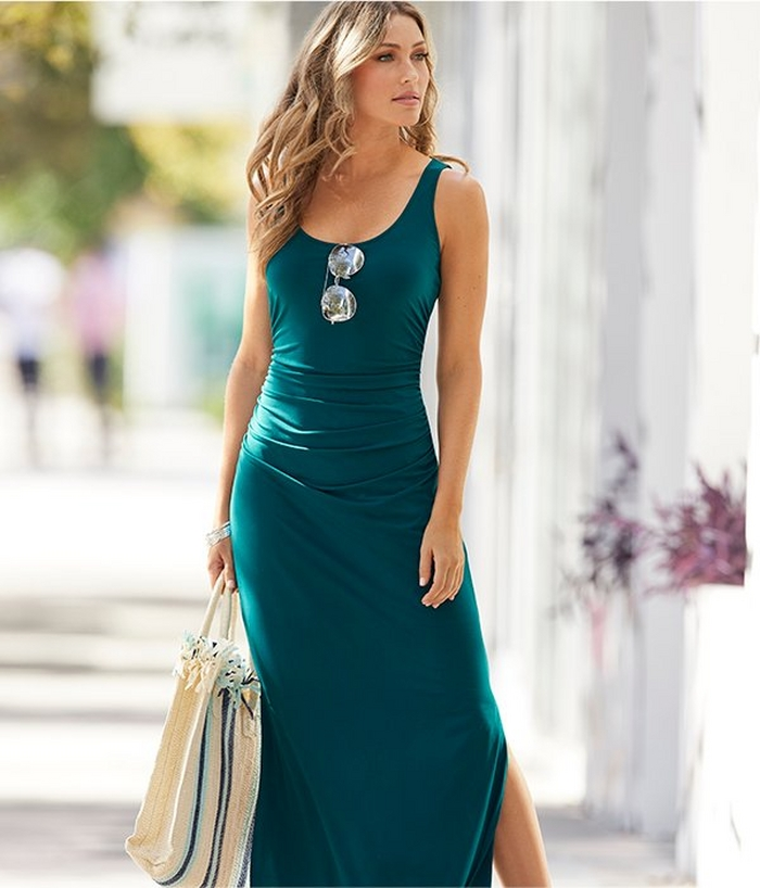 model wearing a teal ruched maxi dress, mirrored sunglasses, and a blue and white striped beach bag.