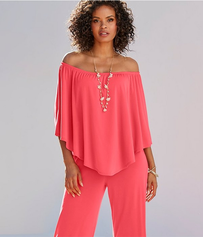 model wearing an off the shoulder coral jumpsuit and long necklace.