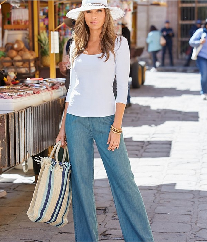 model wearing a white scoop neck three-quarter sleeve top, chambray pull-on pants, a white hat, and a blue and white striped beach bag.