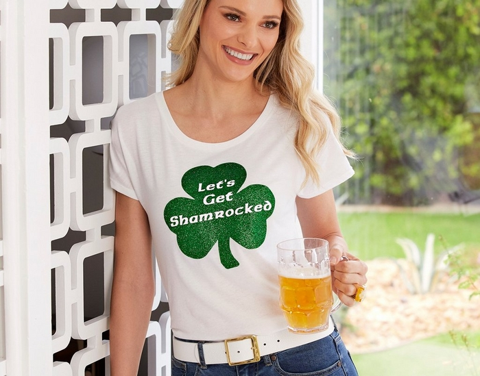 model wearing a white tee shirt with a glittery green shamrock that says, 'lets get shamrocked' while holding a mug of beer.