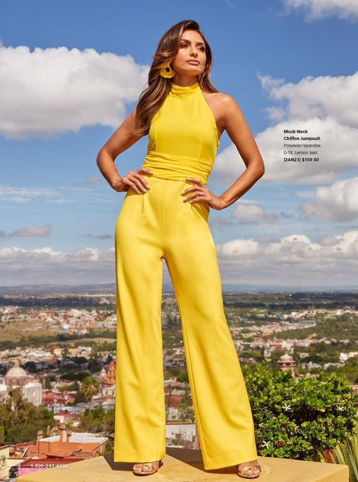 model wearing a mock-neck yellow jumpsuit, simple gold heels, and yellow earrings.