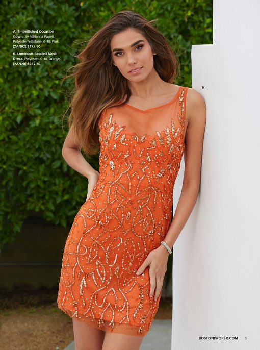 model wearing a luminous beaded mesh dress in orange.