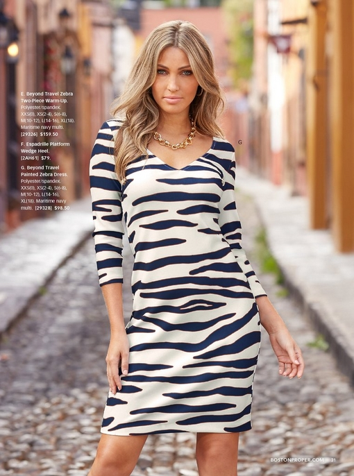 model wearing a navy and white zebra print three-quarter sleeve dress and a gold chain necklace.